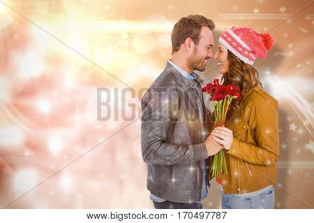 Young couple holding flowers against glowing background