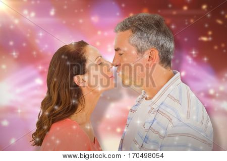 Profile view of couple about to kiss against glowing background