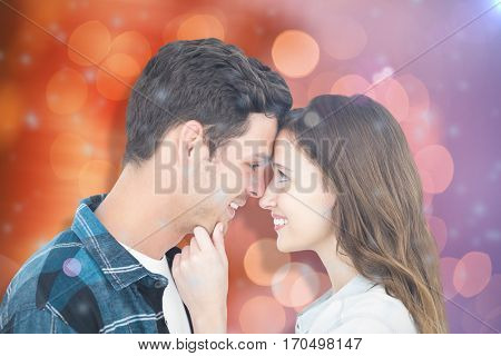 Couple with head against head and holding chin against glowing background