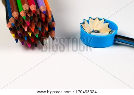 Multicolored pensils and pencil sharpener in the box on the paper.Back to school. Copy space. Top view.