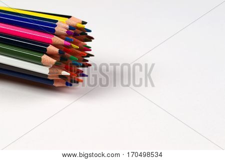 Multicolored pensils and elastic in the box on the white paper. Back to school. Copy space. Top view.