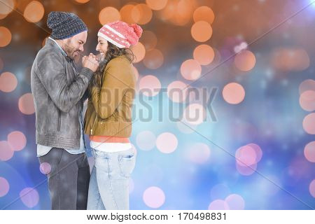 Young couple in warm cloth standing face to face and shivering against glowing background