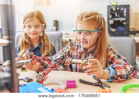 Hilarious girls are sitting together near working desk in workshop. They showing ready flying drone