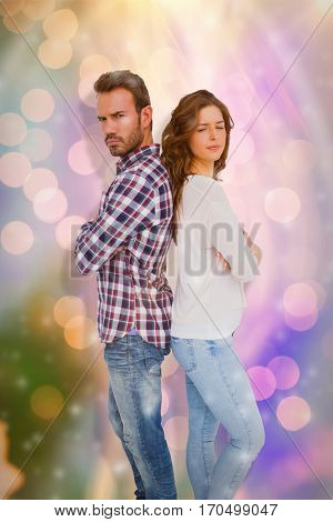 Depressed couple standing back to back against glowing background