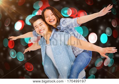 Portrait of happy couple with arms outstretched against digitally generated twinkling light design