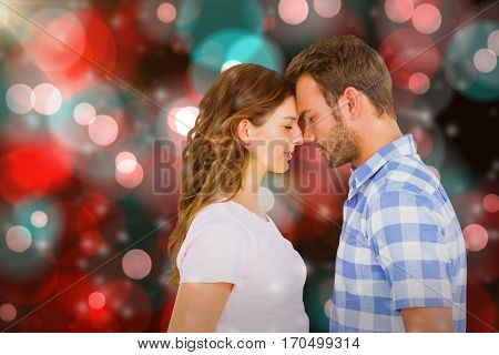 Young couple rubbing nose against digitally generated twinkling light design