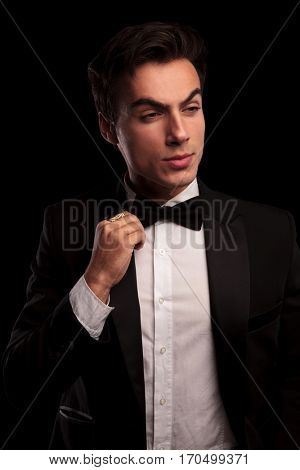 portrait of an elegant man in tuxedo fixing his bowtie and looks to side on black background