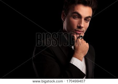 elegant handsome man in tuxedo holding his chin and thinking on black background