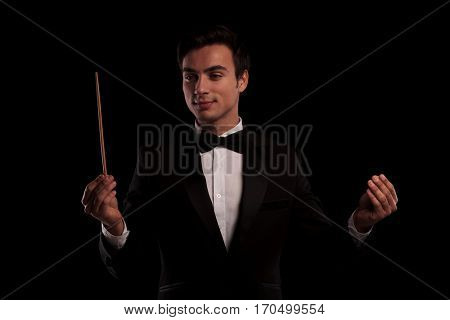 elegant man in tuxedo conducting an orchestra , business concept, on black studio background