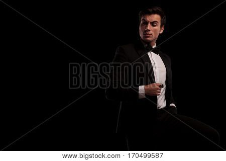 arrogant young man in tuxedo and bowtie looking back over his shoulder on black backogrund