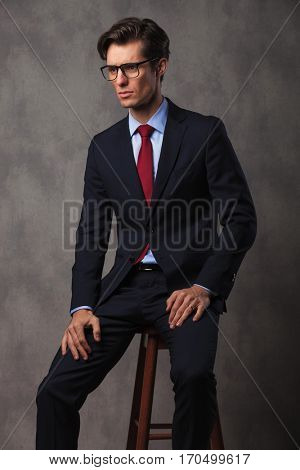 side view picture of a seated business man with glasses and hands on knees looking away from the camera in studio