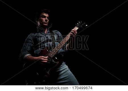 passionate young guitarist playing on dark studio background