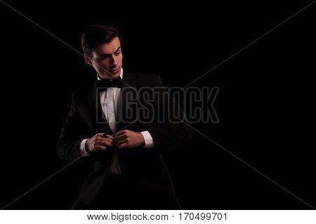 side view of an elegant man buttoning his tuxedo and looks to side on black background