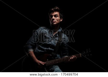 young man in jeans jacket playing electric guitar and looks to side on black background