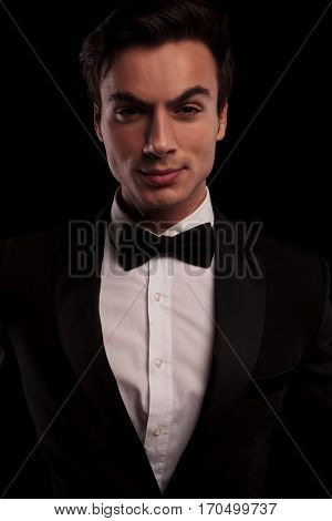 serious sexy man in tuxedo posing for the camera on black studio background
