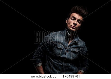 arrogant young man in jeans jacket standing on black studio background