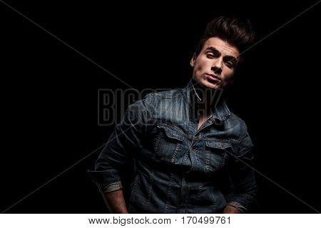 arrogant young man in jeans jacket standing on black studio background