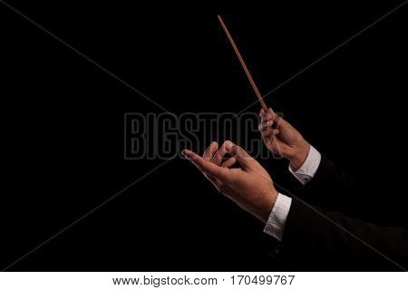 conductor's hands conducting an orchestra on black studio background