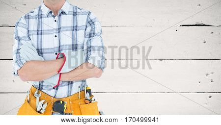 Mid section of handyman with tool belt and drill machine against wooden wall
