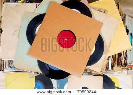 Retro styled image of a collection of old vinyl record lp's with sleeves on a wooden background. Top view. Copy space.