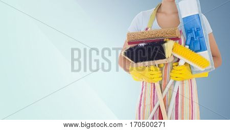Mid-section of female cleaner holding brushes against blue background