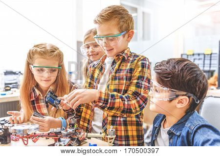 Interested smiling team of creators is around table. Hilarious boy standing among others and holding mainboard