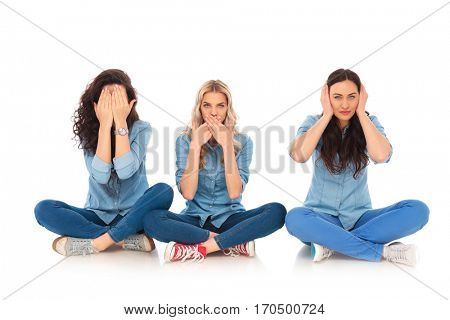 three young women making the no evil poses sitting on white background