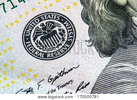 macro photo of federal reserve system symbol on hundred dollar bill, shallow focus