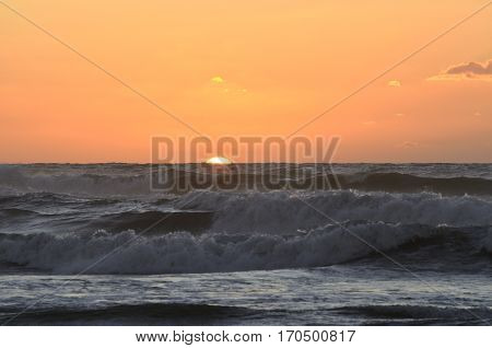 Sunset on the beach of the solar disk dive to half in the sea waves