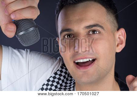 Young Male Black-haired Pop Singer Performs With Microphone