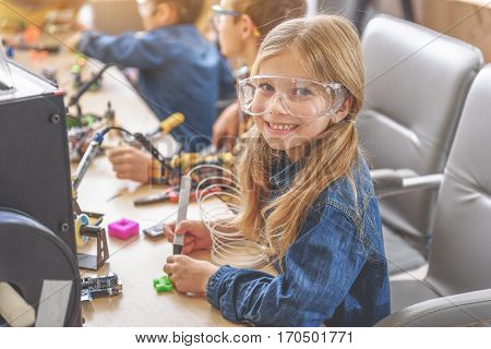 Hilarious little girl is sitting near wooden desk. She holding special instrument and looking at camera with bright smile