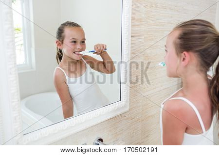 Happy girl brushing her teeth in bathroom at home