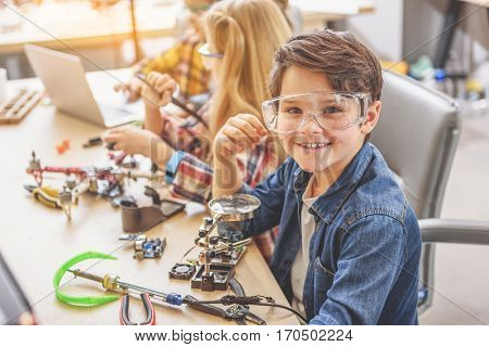 Hilarious boy is sitting near wooden desk, full of tools and details. He looking at camera