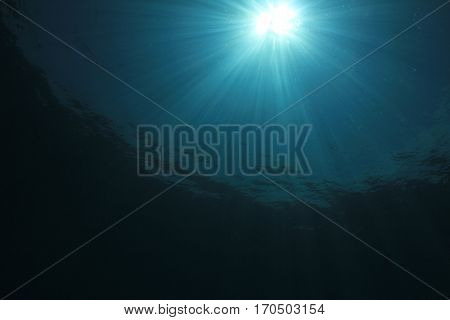 Underwater ocean background. Sunlight in sea water