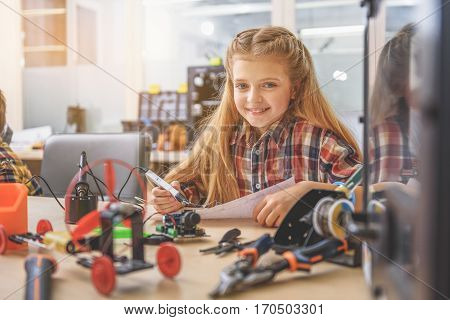 Hilarious girl is sitting near wooden board and holding paper with special tool for drawing. She looking at camera