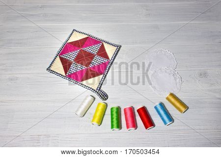 The kitchen cloth potholder for housewives and colorful threads on wooden table