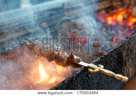 Spit roasted meat being fried on a charcoal grill