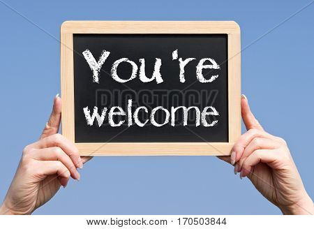 You are welcome - female hands holding chalkboard with text