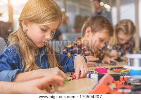 Concentrated children are sitting at wooden desk. They working with different tools and compiling appliances