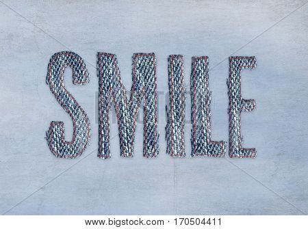 word smile in blue denim fabric with red outline stitching