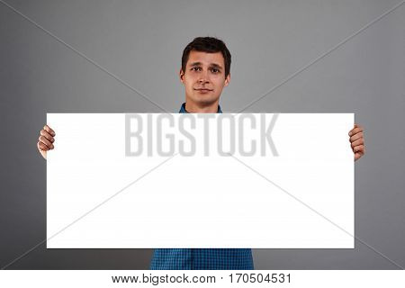 Handsome man holding white paper poster copy space screen in two hands. Rectangular list for text or advertising goods. Atractive guy holding a banner.