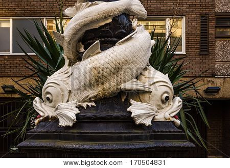 characteristic decoration around a street lamp in London large ornaments in the shape of a fish decoration of the central city of London