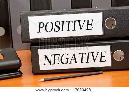 Positive and Negative - two binders on desk in the office