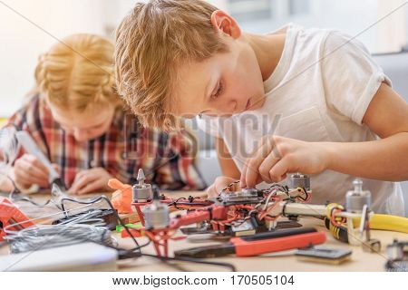 Attentive boy is sitting at wooden desk and renovating flying drone. Girl making diy
