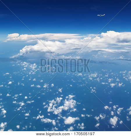 Oncoming flight traffic in mid air. Aircraft flying above ocean beautiful white cloud. Clear blue sky aerial view from cabin through plane window. Vacation tour travel background with copy space