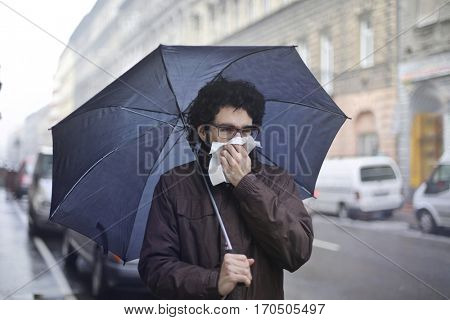 Man blowing his nose under his umbrella on the street