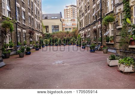 beautifully landscaped plaza between the buildings in the city center a large blue pot