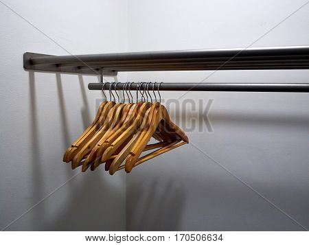 Wooden clothes hangers on a metal rack in a wardrobe dressing room