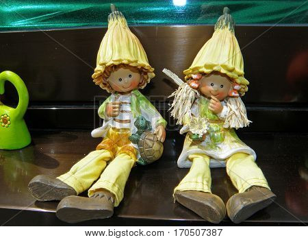Little Boy with Turtle and Girl with Flower Figurines in Yellow Outfit and Hat sitting Side by Side