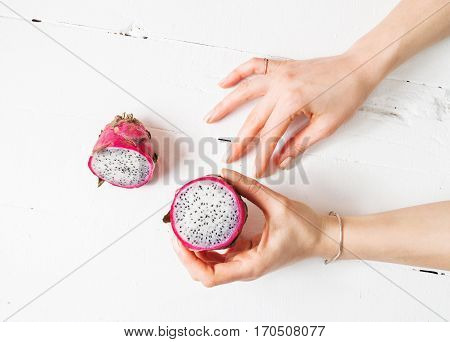 Female hands and Juicy pink pitaya on wooden table.